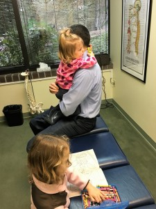 Dr. Cummins adjusting his own children at Bellevue's Cummins Chiropractic.