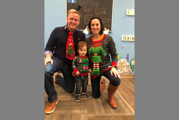 Dr. Scott with a baby and mom in festive outfits.