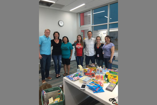 The staff standing behind a table with school supplies on it.