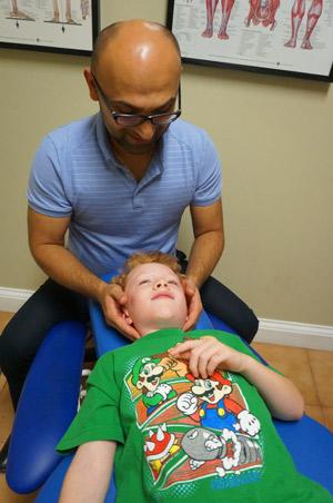 Dr. Yako Merogi, Chiropractor Chiropractor, Dr. Merogi adjusting child