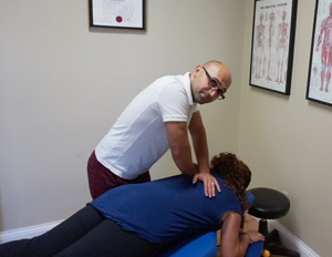 Body Cure Sport and Therapy Chiropractor, Dr. Mergoi adjusting woman