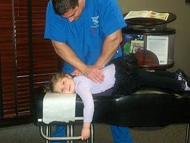 Dr. Darrin adjusting a child.