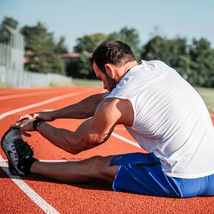 athlete stretching leg on track
