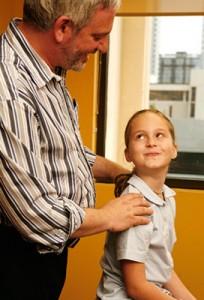 Dr. Starkman adjusting a child