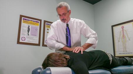Dr Cutsinger adjusting woman's midback