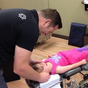 Dr. Tim adjusting a child
