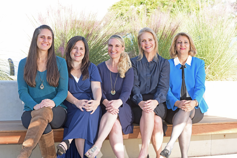 The Angell Chiropractic and Wellness Center team sitting on a bench outside.