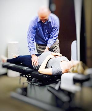 Dr. Thomas Tuzzolino adjusting pregnant woman