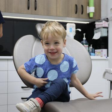 Boy at children's dentist receiving dental hygiene for kids