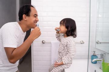 Girl brushing teeth with dad teaching child dental health tips