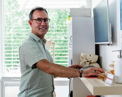 Dr. Roberto sitting at desk