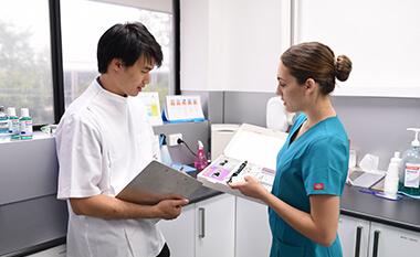 Dentist conferring with dental hygientist