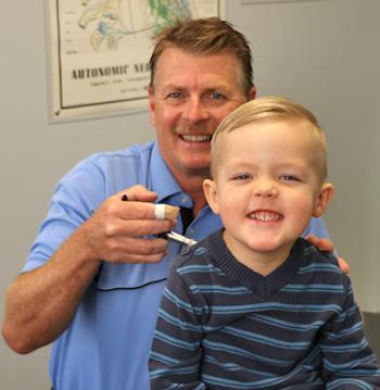 Dr. Bob adjusts a child