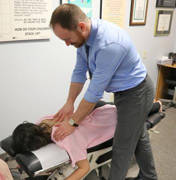 Dr. Aaron adjusts a patient
