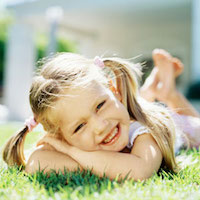 happy young girl laying outside