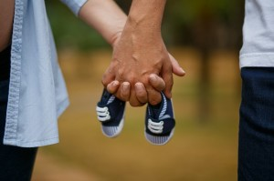 mom and dad holding hands with baby shoes