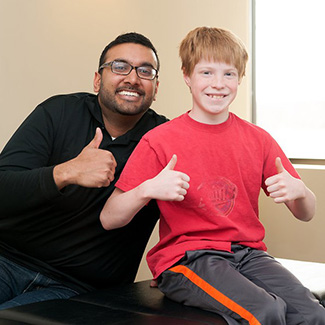 Dr. Dave and teenage boy giving thumbs up