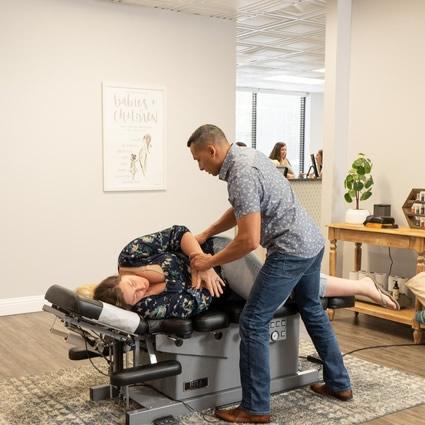 Dr Eric adjusting female patient