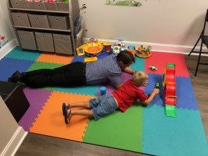 chiropractor and young child playing on a mat together