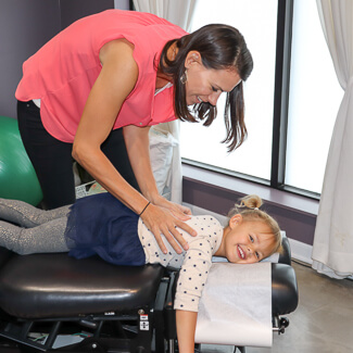 Dr. Andrea adjusting small girl's thoracic area