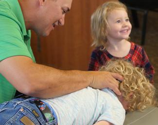 Dr. Phil adjusting a child