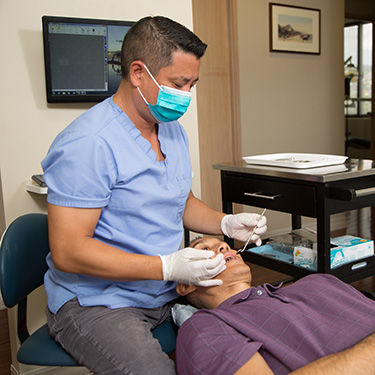 Dentist examing patients gums