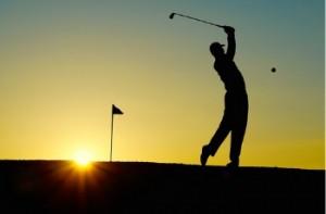 Man golfing at sunset