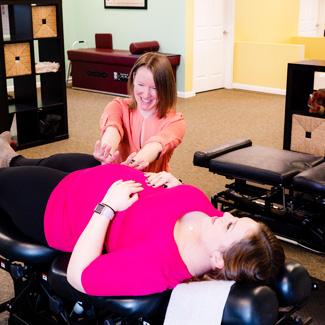 Dr. Carrie adjusting pregnant mom