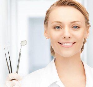 Woman dentist holding instruments
