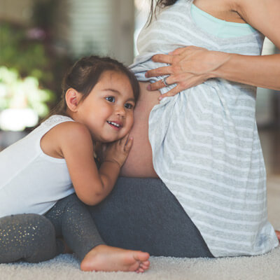 Little girl with head on pregnant belly