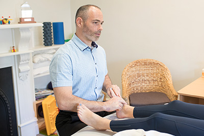 Dr DeMaio assessing a patient's foot