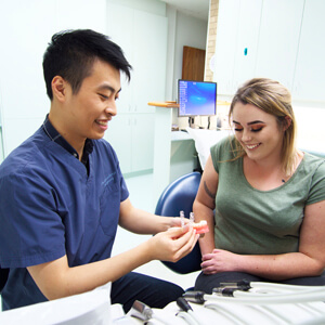 Dr Tao demonstrating invisalign braces to patient