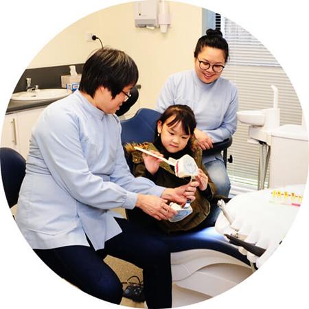 Dr Li demonstrating proper tooth brushing to little girl