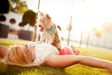 woman-with-dog-laying-on-grass