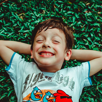 boy laying on grass smiling