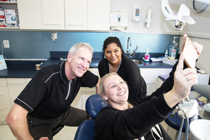 Dr Raymond taking selfie with patient and hygienist