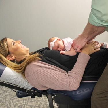 Dr. Thacker adjusting infant