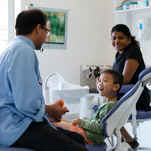 Dr Sav and assistant with young boy in dental chair