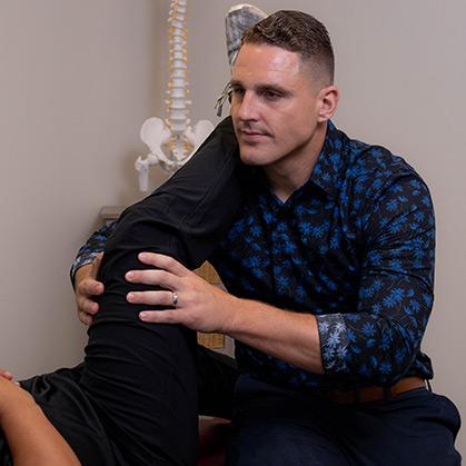 Doctor adjusting patient's leg