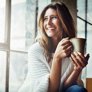 Woman sitting near window drinking coffee
