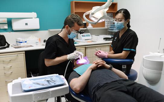 Dr Stuart with assistant performing procedure on patient