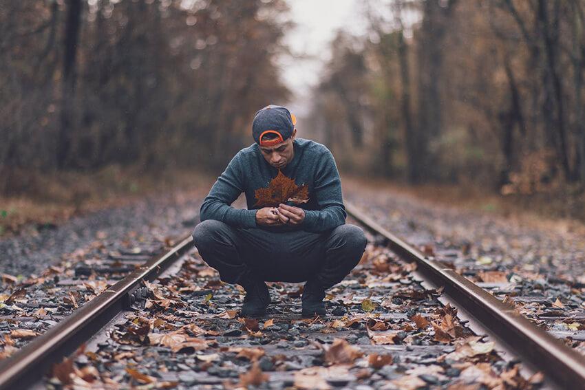 Man kneeling on train track