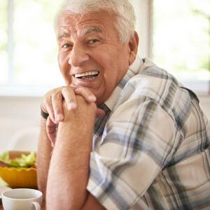 Elderly gentleman sitting at kitchen table