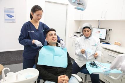 Dental assistant preparing patient for treatment