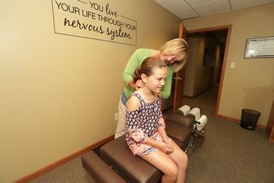 Dr. Becker adjusting girls neck