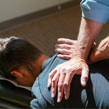 close-up of Dr. Jack adjusting a male patients back