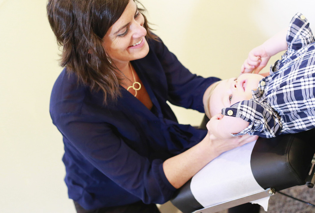 Dr. Micaela adjusting little girl neck