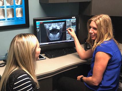 Dr Tonya pointing at computer screen