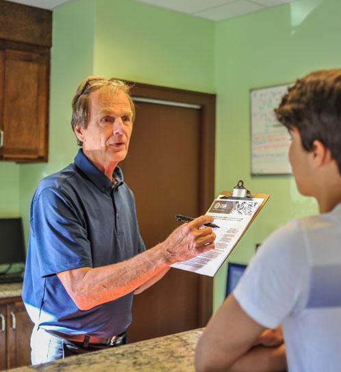 Dr. Joe handing patient paperwork