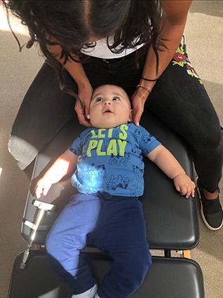 Dr. Ali adjusting baby on table
